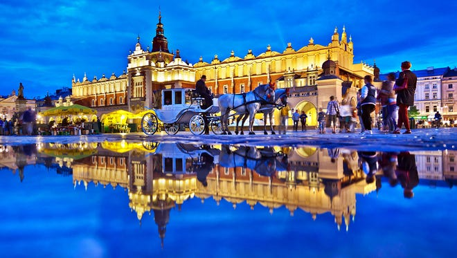 A rain puddle reflects the floodlit charm of Cloth Hall, one of several major buildings on Krakow's Main Market Square.