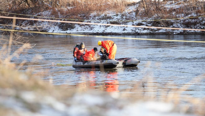 Recovery crew attempts to hook submerged car with tow-line in Cambridge on Monday.