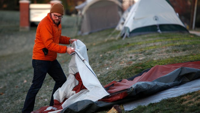 Dustin Nimmo of Mt. Washington breaks down his tent after camping out for ten days in the front yard of Sands Montessori, just a few meters away from Corbly Road. Nimmo was camping out for his 4-year-old daughter, who will be in kindergarten next year. He was relieved, not only because he survived 17-degree temperatures,and a tornado warning, but that his wife, who is pregnant and due Thursday (the day after enrollment), didn't go into labor before the wait was over.