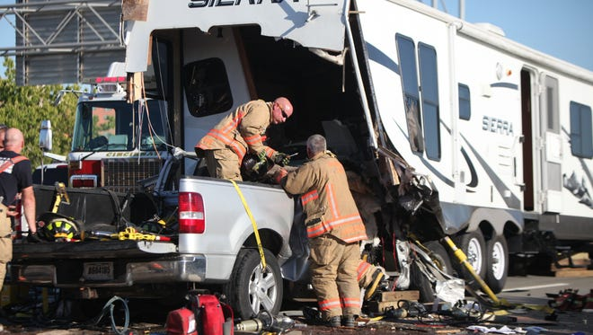 Firefighters work to separate a truck that had rear ended a camper trailer on Interstate 75 closing the highway for about an hour and half.