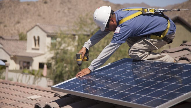 Harmon Solar's John Romer installs solar panels on a Buckeye home in 2013.