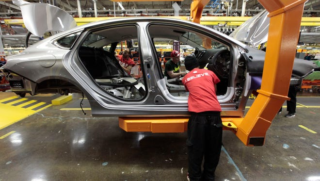 In this March 14, 2014 file photo, assembly line workers build a 2015 Chrysler 200 automobile at the Sterling Heights Assembly Plant in Sterling Heights, Mich.