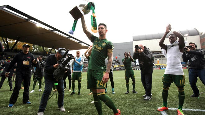 Portland Timbers defender Liam Ridgewell raises the Cascadia Cup after the Timbers defeated Vancouver Whitecaps, 2-1, at Providence Park.