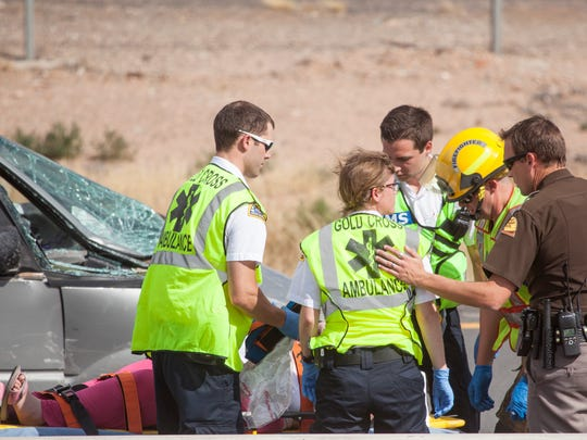 Utah Highway Patrol troopers and Gold Cross paramedics care for a woman involved in an accident in I-15 near mile 6 Friday, July 31, 2015.
