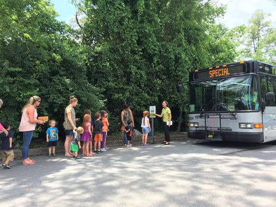 "The KAT bus parked in the Fountain City branch library parking lot for a special Summer Reading Club story time. Participants lined up at the ""bus stop"" before boarding the bus."