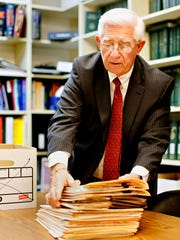 Attorney Donald Reihart gathers folders, which are