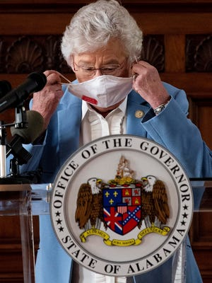 Gov. Kay Ivey removes her mask as she asks citizens to continue wearing masks and use social distancing during a coronavirus update in the state Capitol building in Montgomery, Ala., on Tuesday.