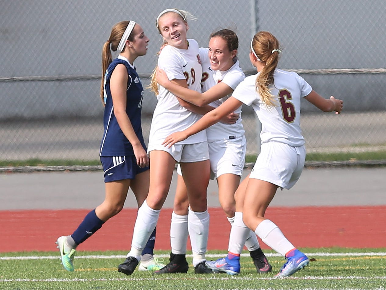 Arlington's Meggie Buttinger is flanked by teammates celebrating her first-half goal against Suffern during the Section 1 Class AA championship game at Yorktown High School on Sunday.