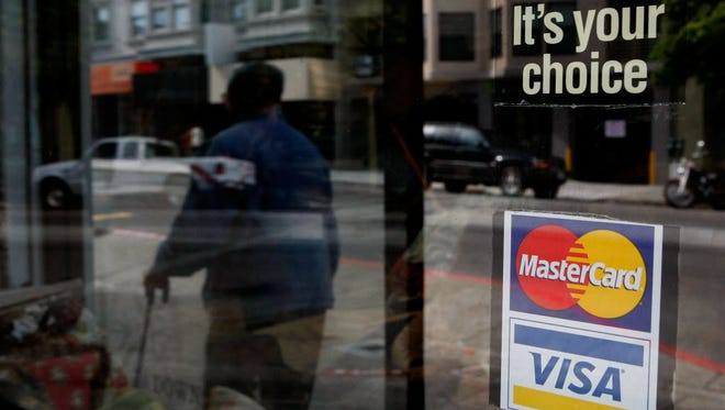 A window sticker advertising Visa and MasterCard credit cards hangs in a window in San Francisco, California.
