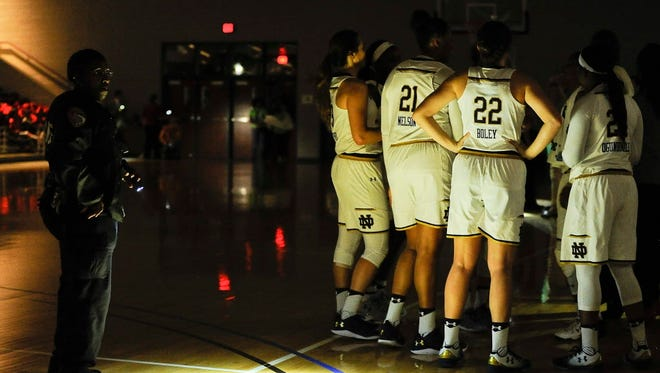 Notre Dame forward Erin Boley (22) and teammates huddle after play was stopped due to a power outage during the first half.
