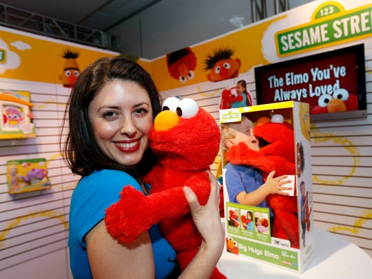 Demonstrator Patricia Santomasso welcomes Big Hugs Elmo at the American International Toy Fair, Friday, Feb. 8, 2013, in New York.