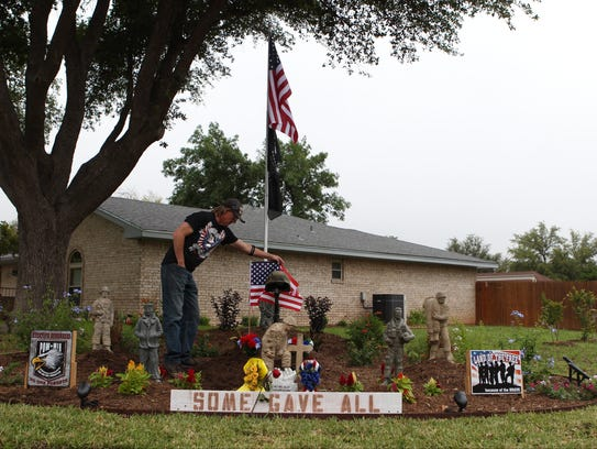 Michelle Gaitan /Standard-Times Michael James Hughes fixes an American flag that is part of his Fallen Solider display in a memorial garden he set up for his wife, veterans and active duty military in honor of Memorial Day.  shot/archived 05-22-2015