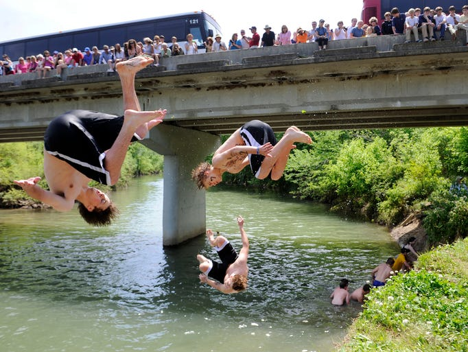 Members of the Greer team make the leap into the West Harpeth river as onlookers watch from the Hwy 96 bridge after falling to Plato in BGA's annual Tug, a tug-of-war contest, Monday, May 5, 2014 in Franklin, TN.