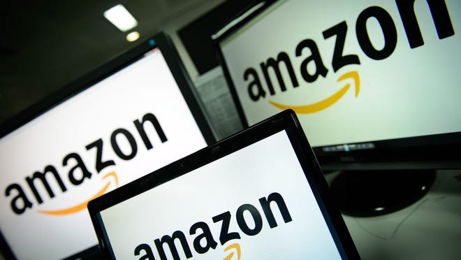 A picture shows the logo of the online retailer Amazon dispalyed on computer screens.
