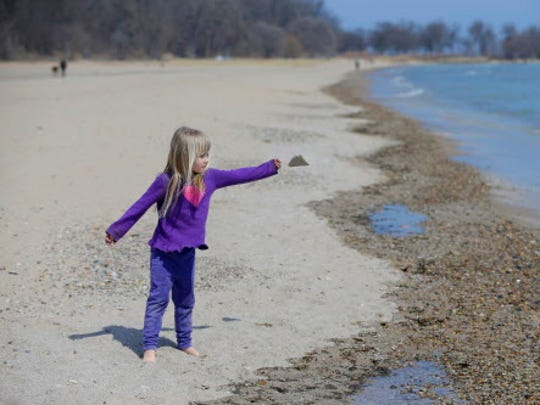 Four-year-old Lily Anna Isabella LaTona, of Glendale throws a rock into Lake Michigan.