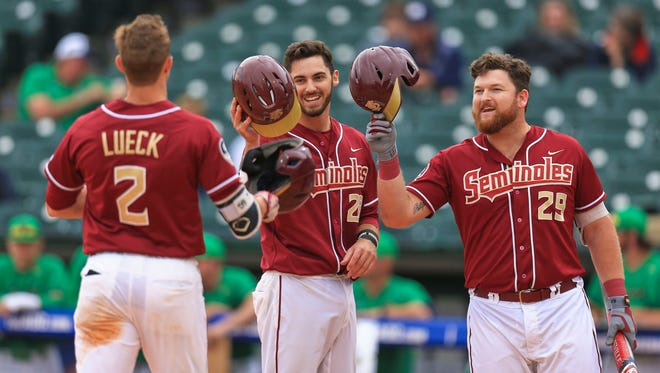 Florida State's Jackson Lueck is congratulated by teammates Dylan Busby, center, and Quincy Nieporte after his two-run homer against Notre Dame on Wednesday in Louisville.