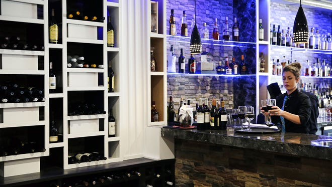 Anastacia Maynard prepares an order of wine in the relocated Il Angolo in downtown Appleton.