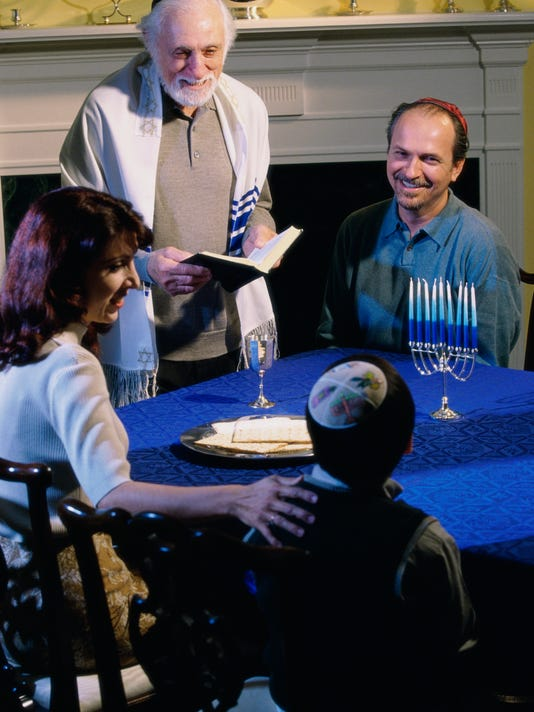Parents and their son and a rabbi at a Hanukkah ceremony