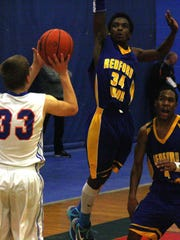 Redford Union's Keyon Thomas elevates high to block a Garden City shot Tuesday night.