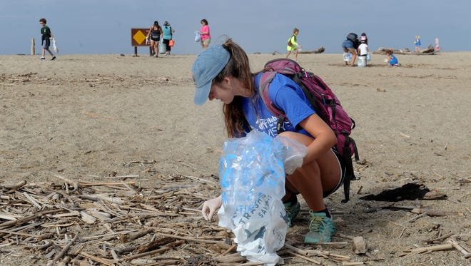 Melanie Buckovec, of Thousand Oaks, picks up foam pieces during last year's Coastal Cleanup Day efforts at Mugu Rock along Pacific Coast Highway.