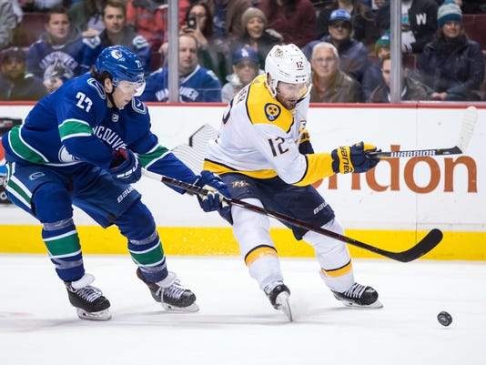 Nashville Predators' Mike Fisher, right, skates with the puck while being checked by Vancouver Canucks' Ben Hutton during the first period of an NHL hockey game Friday, March 2, 2018, in Vancouver, British Columbia. (Darryl Dyck/The Canadian Press via AP)