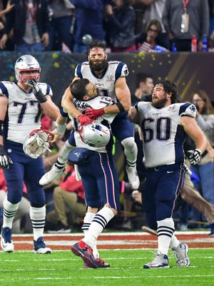 Feb 5, 2017; Houston, TX, USA; New England Patriots quarterback Tom Brady (12) celebrates with wide receiver Julian Edelman (11) after winning Super Bowl LI as tackle Nate Solder (77) and center David Andrews (60) look on. The Patriots defeated the Atlanta Falcons 34-28 at NRG Stadium. Mandatory Credit: Bob Donnan-USA TODAY Sports