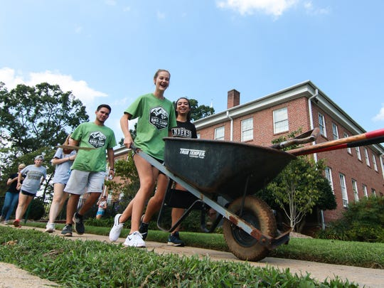Meagan McGinley (right) pushes a wheelbarrow near classmates helping landscape at Boulevard Baptist Church in Anderson. The students helped in the community as part of the school service day.