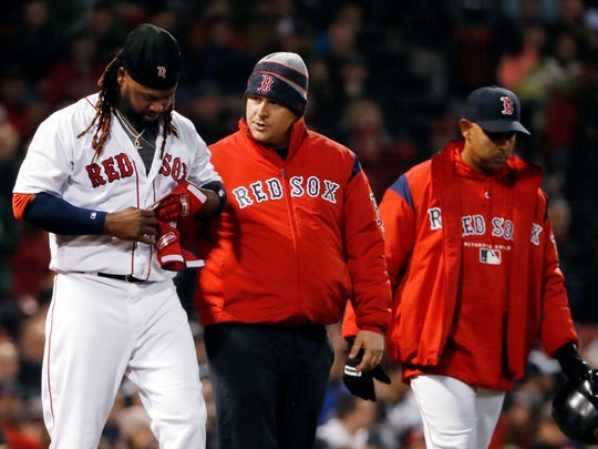 Boston Red Sox's Hanley Ramirez has his hand looked at by a trainer after being hit by a pitch as Boston Red Sox manager Alex Cora, right, watches during the first inning of a baseball game against the New York Yankees at Fenway Park in Boston on Thursday, April 12, 2018.