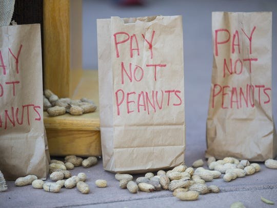 "Bags titled ""Pay not peanuts"" sit underneath the podium"