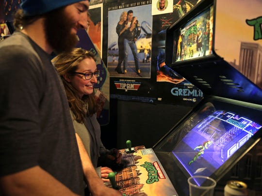 "Jordan Mosher, left, and Brooke Whitten play ""Teenage Mutant Ninja Turtles"" at Player 2 Arcade Bar during the opening weekend in downtown Appleton."