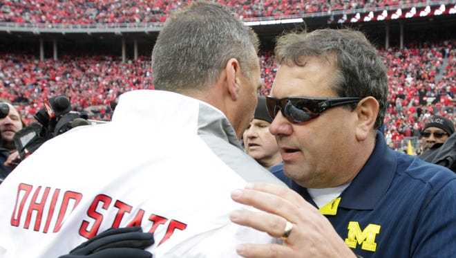 Michigan football coach Brady Hoke, right, shakes hands with Ohio State coach Urban Meyer after a game Nov. 29, 2014, in Columbus, Ohio.