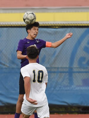 New Rochelle's Felipe Tobon, top, heads the ball during Saturday's Class AA regional final against Newburgh.