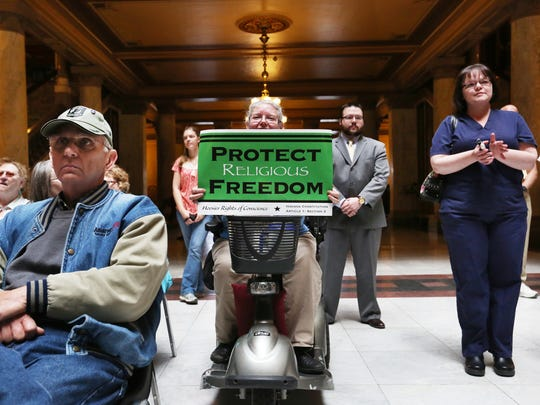 "Cindy Holmes of Mechanicsburg, Ind., holds up a sign at the Indiana Pastors Alliance rally in the north atrium of the Indiana Statehouse on April 27, 2015. More than 150 people showed up to express their opposition to the ""fix"" that Indiana lawmakers made to the Religious Freedom Restoration Act."