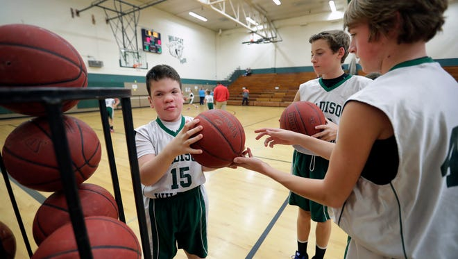 Team manager Cameron Howard, left,  collects basketballs from Michael O'Hagen and Aidan O'Hagen, right, during a boys' basketball game against Einstein Middle School Tuesday at Madison Middle School.