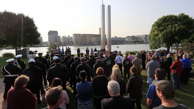 Law enforcement, fire fighters, and community members gather for a decommissioning ceremony for the 9/11 monument on Monday, Sept. 11, 2017 in Green Bay, Wis. City Council members voted unanimously in August to remove the memorial due to its deterioration and inaccuracies information on it.