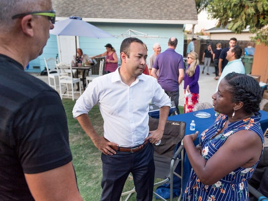 Democratic congressional candidate Andrew Janz, center, talks with Patrick Mendes, left, Sandra Mathis of Tulare and other supporters during a barbecue at a Visalia home on Friday, July 13, 2018.