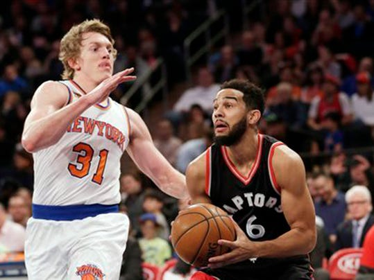 FILE - In this April 9, 2017, file photo, Toronto Raptors' Cory Joseph, right, drives past New York Knicks' Ron Baker during the first half of an NBA basketball game in New York. Three people with knowledge of the dealings tell The Associated Press that the Raptors have made two trades, sending DeMarre Carroll to Brooklyn for salary cap relief and landing C.J. Miles in a sign-and-trade with Indiana for Joseph. (AP Photo/Seth Wenig, File)