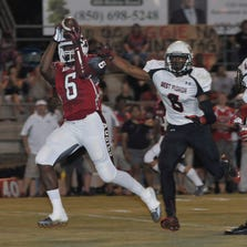 Dee Thompson of Tate hauls in this long pass and takes it for a TD in the first few minutes of the Tate Aggies game against West Florida High at Tate Friday night.  Defending on the play for the Jags is Kelsey Stokes, No. 8, and Adarius Purifoy.  Tate won 19-7.