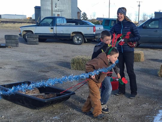 Grant Holzer and Hunter Wichman drag a calf sled of