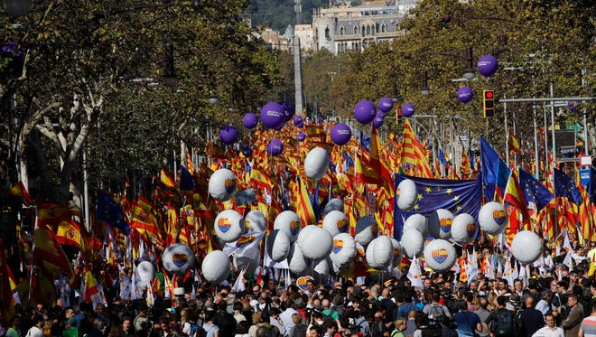 Nationalist activists march with Catalan, Spanish and European Union flags during a mass rally against Catalonia's declaration of independence, in Barcelona, Spain, Sunday, Oct. 29, 2017.