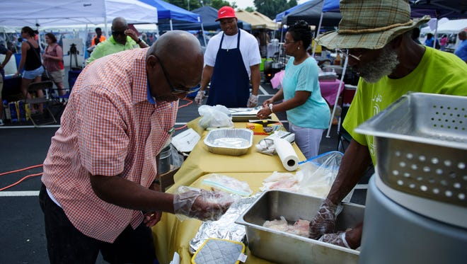 Joerome Hawkins, left and James McBride prepare fish for frying at Family Day in the Park at the C.K. Newsom Center in 2013.