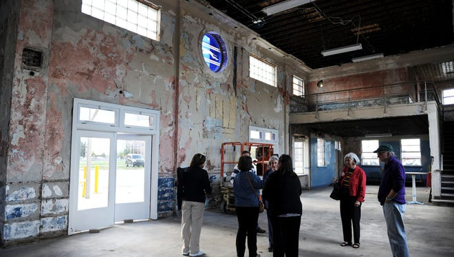 EMILY BROUWER / COURIER & PRESS People talk inside the old Greyhound Station in Evansville before the announcement for a new pub, Bru Burger. Bru Burger opened last year.  Stephanie Richard and Michael Martin of Architectural Renovators were part of the team that renovated the building, and they will be the keynote speakers at Downtown Henderson Partnership's annual awards breakfast on March 23.