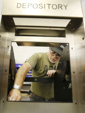 Mark Hedger works on a night depository, used by banks, allowing customers to deposit money overnight, at the Hamilton Safe Company in Mason.