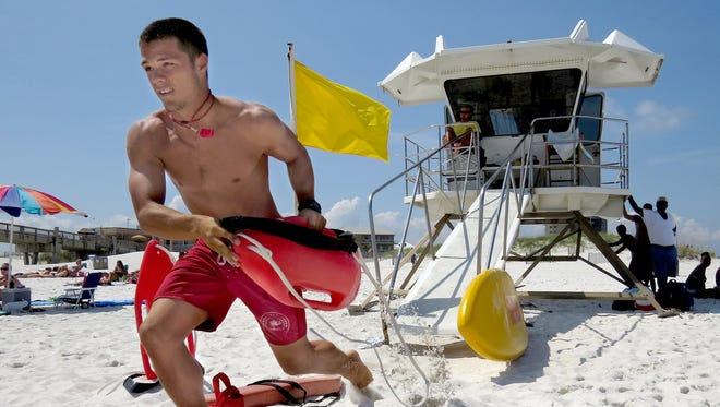 Pensacola Beach lifeguard A.C. Jeter grabs his flotation device during a training demonstration on Casino Beach as he heads for the water to ?rescue? a fellow lifeguard playing the part of a drowning victim.   Photos by Bruce Graner/bgraner@pnj.com Pensacola Beach lifeguard A.C. Jeter grabs his flotation device on the run during a rescue training demonstration