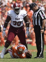Troy defensive tackle Trevon Sanders (90) stands over Clemson quarterback Deshaun Watson (4) after a play during the first half on an NCAA college football game on Saturday, Sept. 10, 2016, in Clemson, S.C. (AP Photo/Rainier Ehrhardt)