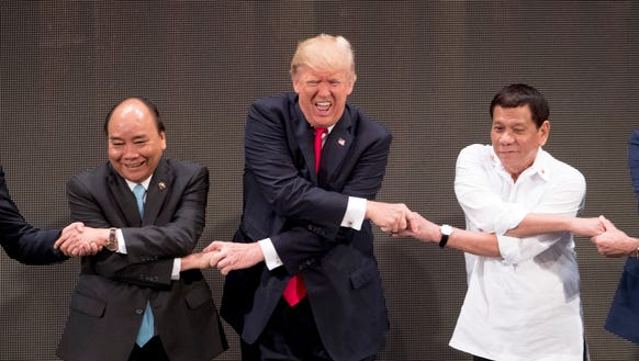 "President Trump, center, reacts as he does the ""ASEAN-way"