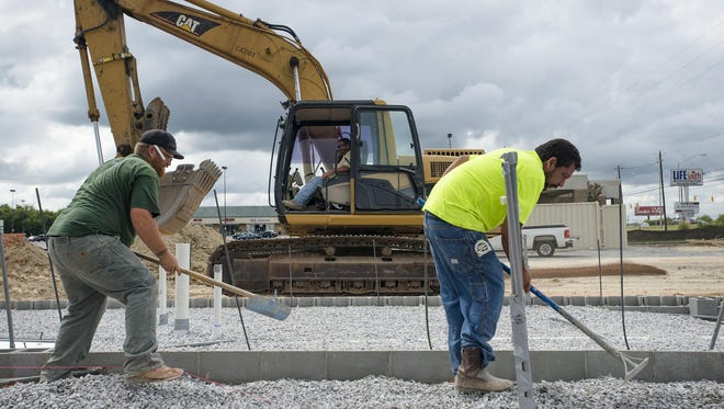 mployees of 31 Construction James Burnett, left, and Alejandro Morales work on the foundation of Mr. K Car Wash in September. The business expects to open in February.