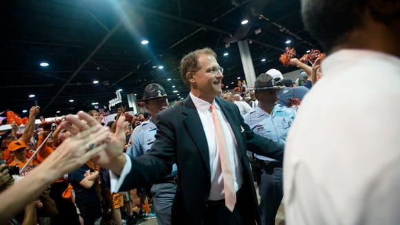 Auburn head coach Gus Malzahn high fives fans during Tiger Walk before the NCAA football game between Auburn and Louisville on Saturday, Sept. 5, 2015, in at the Georgia Dome in Atlanta, Ga.