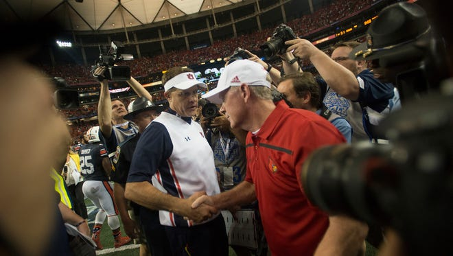 Auburn head coach Gus Malzahn greets Louisville head coach Bobby Petrino after Auburn defeated Louisville 31-24 on Saturday, Sept. 5, 2015, in at the Georgia Dome in Atlanta, Ga.