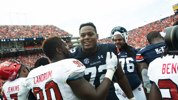 Auburn Tigers offensive lineman Shon Coleman (72) embraces Jacksonville State Gamecocks defensive end Chris Landrum (90) after Auburn defeated Jacksonville State Gamecocks 27-20 in overtime on Saturday, Sept. 12, 2015, in at Jordan-Hare Stadium in Auburn, Ala.